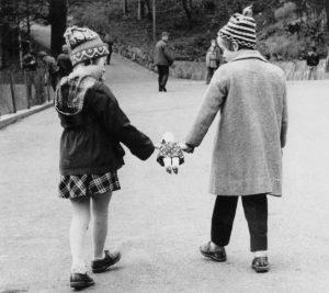 To barn holder en dukke mellom seg på gata. Fra Bakkebø. Foto: Vilhelm Feyling