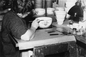 En kvinnelig arbeider påfører gullrand på bolle. Emaljesalen, 1950-årene