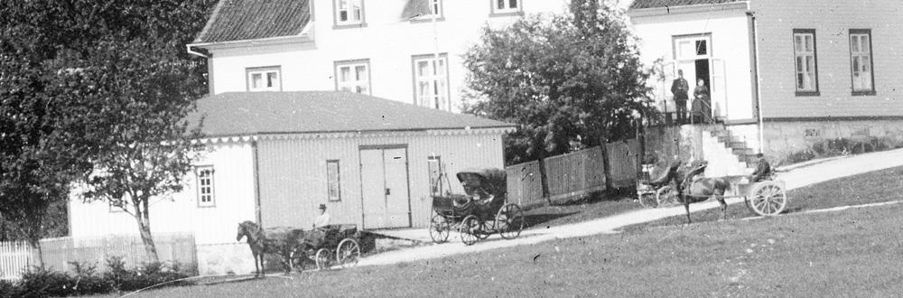Hester og kjerrer på Slettebø gård rundt 1900. Museets resepsjonsbygg er i dag vognskjulet til venstre i bildet. Hovedhuset på museets anlegg på Slettebø er det store huset midt i bildet. Foto: E. H. Torjusen