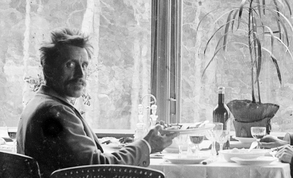Erik Hadland Torjusen sitter ved et bord mot et vindu, vender seg mot kameraet og holder en tallerken. Ukjent sted. 1887-1903. Foto: Erik Hadland Torjusen, DFF-EHT0285 (utsnitt).